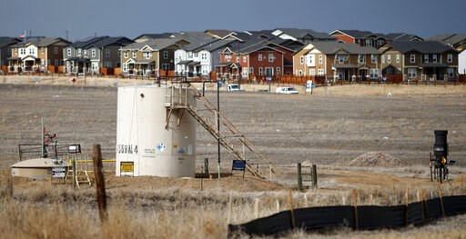 (AP Photo/David Zalubowski, File). FILE - This Feb. 28, 2019 file photo shows a storage tank near a well pad located in a field near a housing development in Broomfield, Colo. The newly reorganized Colorado Oil and Gas Commission planned to meet Tuesda...