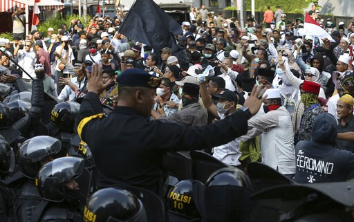 (AP Photo/Achmad Ibrahim). Indonesian police officers block supporters of Indonesian presidential candidate Prabowo Subianto during a rally outside the Elections Supervisory Agency (Bawaslu) building in Jakarta, Indonesia, Tuesday, May 21, 2019. Indone...