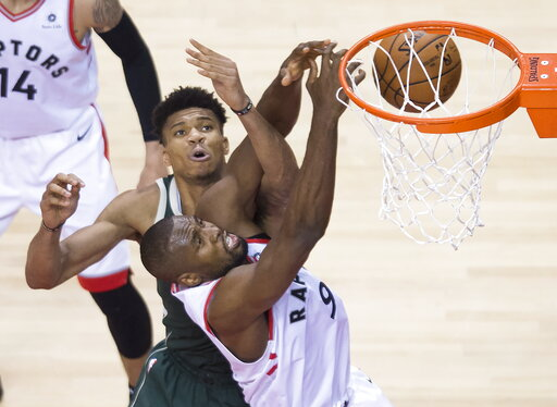 (Nathan Denette/The Canadian Press via AP). Toronto Raptors center Serge Ibaka battles for the ball against Milwaukee Bucks forward Giannis Antetokounmpo during the second half of Game 4 of the NBA basketball playoffs Eastern Conference finals, Tuesday...
