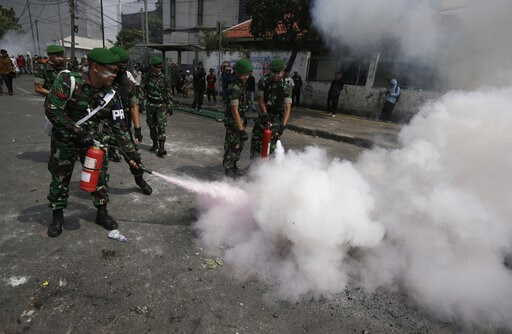 (AP Photo/Dita Alangkara). Indonesian soldiers extinguish burning tires during a clash between protesters and the police in Jakarta, Indonesia, Wednesday, May 22, 2019. Supporters of an unsuccessful presidential candidate clashed with security forces i...