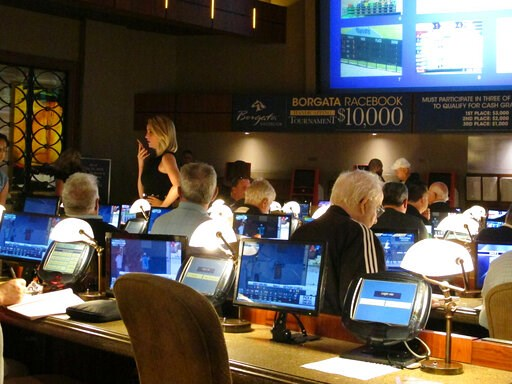 (AP Photo/Wayne Parry). FILE - This June 14, 2018 file photo shows bettors waiting to make wagers on sporting events at the Borgata casino in Atlantic City hours after it began accepting sports bets. On May 22, 2019, the Borgata announced it will spend...