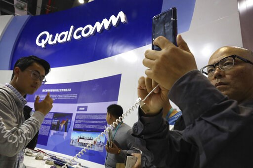 (AP Photo/Ng Han Guan, File). FILE - In this Nov. 6, 2018 file photo, attendees look at the latest technology from Qualcomm at the China International Import Expo in Shanghai. Qualcomm's stock is tumbling before Wednesday's market open on May 22, 2019,...