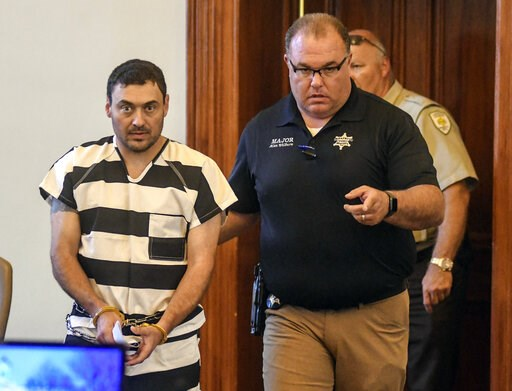 (Bruce Newman/The Oxford Eagle via AP). Oxford Police Officer Matthew Kinne, center, is escorted into a hearing by Lafayette County Sheriff Dept. Maj. Alan Wilburn at the Lafayette County Courthouse, Wednesday, May 22, 2019, in Oxford, Miss. Kinne is c...