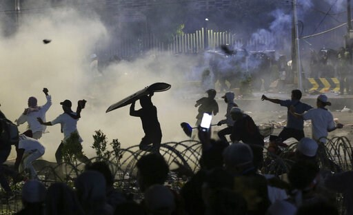 (AP Photo/Achmad Ibrahim). Supporters of the losing presidential candidate throw rocks towards police Wednesday, May 22, 2019, in Jakarta, Indonesia. Indonesian President Joko Widodo said authorities have the volatile situation in the country's capital...