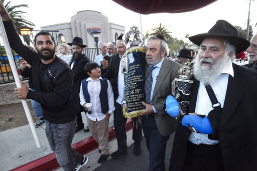 (Hayne Palmour IV/The San Diego Union-Tribune via AP). Howard Kaye, center, husband of Lori Kaye, carries the new Torah as Rabbi Yisroel Goldstein, right, and other members of the Chabad of Poway synagogue celebrate the completion of the new scroll ded...
