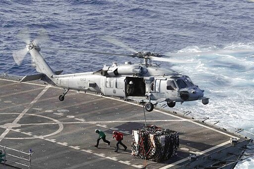 (Mass Communication Specialist 3rd Class Darion Chanelle Triplett/U.S. Navy via AP). In this Sunday, May 19, 2019 photo, an MH-60S Sea Hawk helicopter transports cargo from the fast combat support ship USNS Arctic to the Nimitz-class aircraft carrier U...