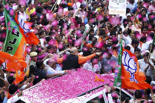(AP Photo/Manish Swarup). India's ruling Bharatiya Janata Party (BJP) President Amit Shah is showered with flower petals as he arrives at the party office in new Delhi, India, Thursday, May 23, 2019. Indian Prime Minister Narendra Modi's party claimed ...