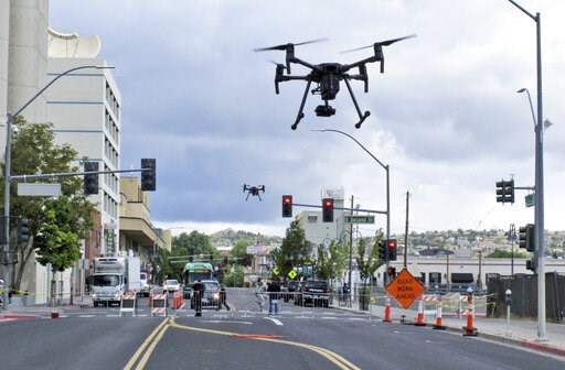 (AP Photo/Scott Sonner). In this May 21, 2019 photo, two drones fly above Lake Street in downtown Reno, Nev., on, as part of a NASA simulation to test emerging technology that someday will be used to manage travel of hundreds of thousands of commercial...