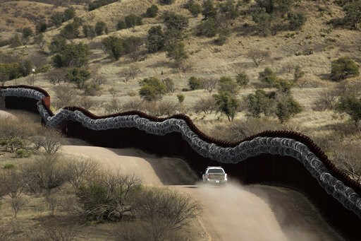 (AP Photo/Charlie Riedel). FILE - This March 2, 2019 photo shows a Customs and Border Control agent patrols on the US side of a razor-wire-covered border wall along the Mexico east of Nogales, Ariz.  A surge of asylum-seeking families that has strained...