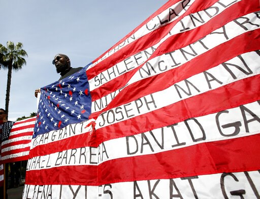 (AP Photo/Rich Pedroncelli, File). FILE - In this April 8, 2019 file photo, Malaki Seku Amen holds up an American flag with the names of people shot and killed by law enforcement officers, as he and others in rally in support of a bill that would restr...