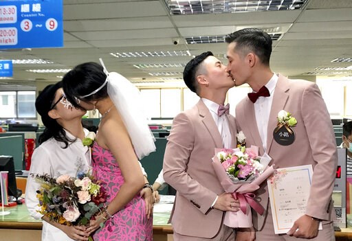 (AP Photo/Johnson Lai). Two same-sex couples seal their legal marriage with a kiss at the registration office in Xingyi District in Taipei, Taiwan, Friday, May 24, 2019. Hundreds of same-sex couples in Taiwan are rushing to the household registration o...
