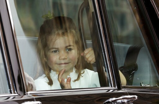(AP Photo/Alastair Grant, file). FILE - In this Friday, Oct. 12, 2018 file photo, Princess Charlotte waves as she arrives by car for the wedding of Princess Eugenie of York and Jack Brooksbank in St George's Chapel, Windsor Castle, near London, England...