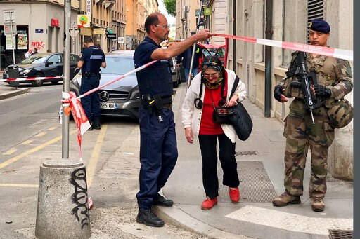 (AP Photo/Sebastien Erome). A police officer lets an elderly woman leaving the area while soldiers secure the access near the site of a suspected bomb attack in central Lyon, Friday May, 24, 2019. An explosion Friday on a busy pedestrian street in the ...