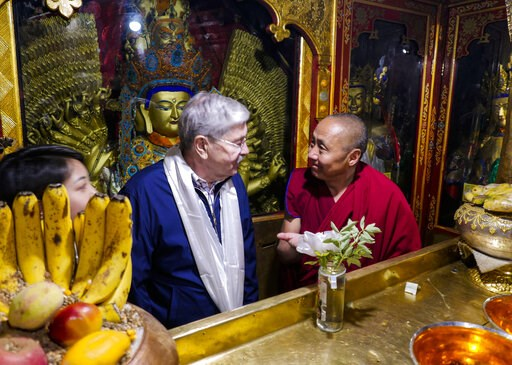 (U.S. Mission to China via AP). In this photo taken May 23, 2019, and released by the U.S. Embassy in Beijing, U.S. Ambassador to China Terry Branstad, left, speaks with a monk at the Jokhang Temple in Lhasa in western China's Tibet Autonomous Region. ...
