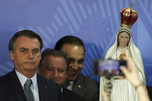 (AP Photo/Eraldo Peres). Brazil's President Jair Bolsonaro poses for photos with a statue of Our Lady of Fatima,during a Catholic ceremony at which he dedicated his nation to the Immaculate Heart of Mary at Planalto presidential palace in Brasilia, Bra...