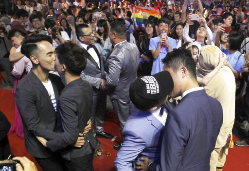 (AP Photo/Chiang Ying-ying). Taiwanese same-sex couples kiss at their wedding party in Taipei, Taiwan, Saturday, May 25, 2019. Taiwan became the first place in Asia to allow same-sex marriage last week. Hundreds of same-sex couples in Taiwan rushed to ...