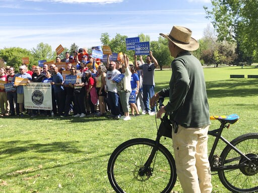 (AP Photo/James Anderson). In this Saturday, June 1, 2019 photo, a passing bicyclist pauses to watch supporters of Denver Mayor Michael Hancock as they pause for a picture during a rally for the incumbent in Denver. Hancock, who is seeking his third, f...