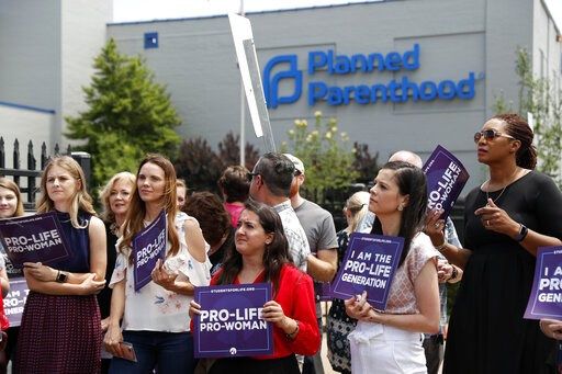 (AP Photo/Jeff Roberson). Anti-abortion advocates gather outside the Planned Parenthood clinic Tuesday, June 4, 2019, in St. Louis. A judge is considering whether the clinic, Missouri's only abortion provider, can remain open.