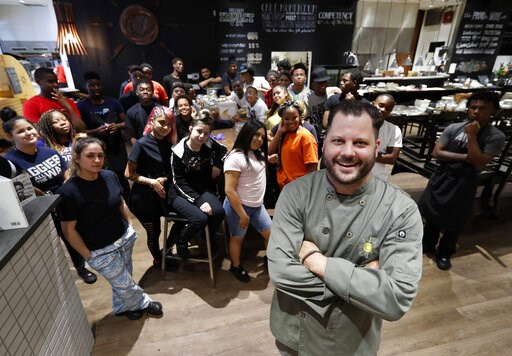 (AP Photo/Tony Gutierrez). Chad Houser, founder and executive chef at Cafe Momentum, poses for a photograph with members of his staff inside the cafe in Dallas, Tuesday, June 4, 2019. Houser said that the lessons learned through training from Stand Tog...