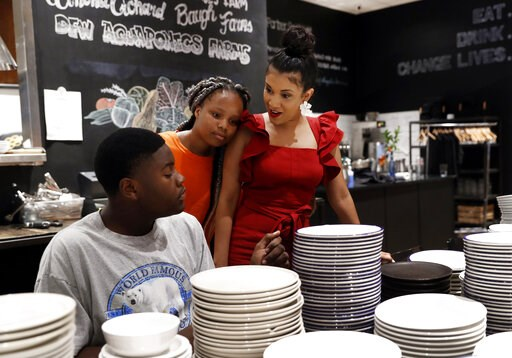 (AP Photo/Tony Gutierrez). Staff member James Reynolds, left, and Brie Guinn, center, talk with Cafe Momentum case manager Kaileigh Johnson, as the two help the entire staff clean the restaurant in Dallas, Tuesday, June 4, 2019. The cafe has benefitted...