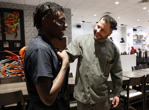 (AP Photo/Tony Gutierrez). Chad Houser, founder and executive chef at Cafe Momentum, laughs as he talks with staff member Marquel Gray, left, at the cafe in Dallas, Tuesday, June 4, 2019. Houser said that the lessons learned from training through Stand...
