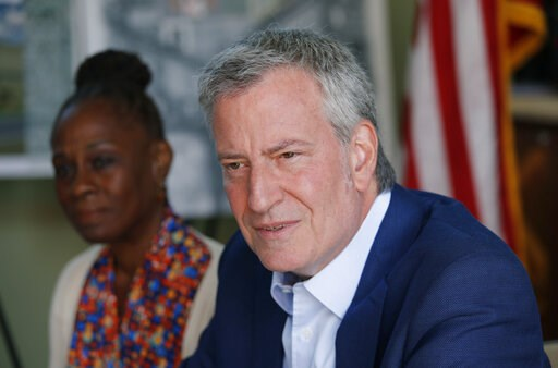 (AP Photo/John Locher). Democratic presidential candidate New York Mayor Bill de Blasio, right, and his wife Chirlane McCray speak with veterans and military families at Veterans Village II, Saturday, May 25, 2019, in Las Vegas.