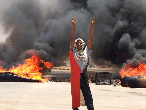 (AP Photo). A protester flashes the victory sign in front of burning tires and debris on road 60, near Khartoum's army headquarters, in Khartoum, Sudan, Monday, June 3, 2019. Sudanese protest leaders say at least 13 people have been killed Monday in th...