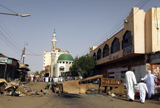 (AP Photo). Sudanese men and a child headed to a mosque navigate a roadblock set by protesters on a main street in the Sudanese capital Khartoum to stop military vehicles from driving through the area on Wednesday, June 5, 2019. The death toll in Sudan...