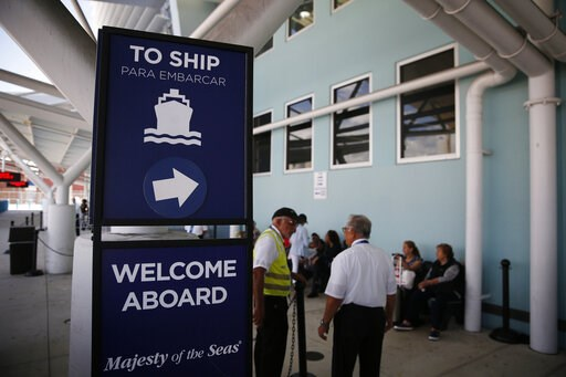 (AP Photo/Brynn Anderson). People stand near a sign directing passengers to a cruise ship at Port Everglades on Wednesday, June 5, 2019, in Fort Lauderdale, Fla. The Trump administration on Tuesday imposed major new travel restrictions on visits to Cub...