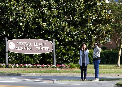 (Kaitlin McKeown/The Virginian-Pilot via AP). FILE - In this May 31, 2019, file photo, women wait by an entrance to the Virginia Beach Municipal Center following a shooting in the public works building in Virginia Beach, Va. Police responding to the de...