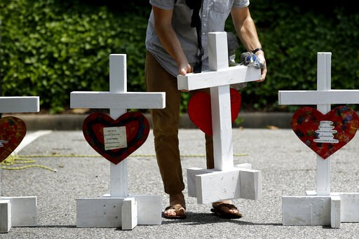 (AP Photo/Patrick Semansky, File). FILE - In this June 2, 2019, file photo, a volunteer prepares to place crosses for victims of a mass shooting at a municipal building in Virginia Beach, Va., at a nearby makeshift memorial. Police responding to the de...