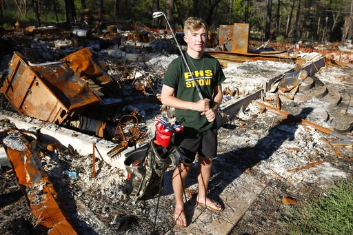 (AP Photo/Rich Pedroncelli). Cade Weins, a senior at Paradise High School, poses with his golf clubs at the burned out ruins of his home in Paradise, Calif., Wednesday, June 5, 2019. When the Camp Fire swept through the area Weins, a member of the scho...