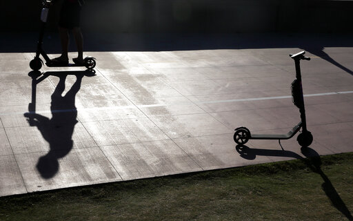 (AP Photo/Gregory Bull, File). FILE - In this May 28, 2019, file photo, a man on a scooter passes a parked scooter along the Mission Beach boardwalk in San Diego. As electric scooters have rolled into more than 100 cities worldwide, many of the people ...