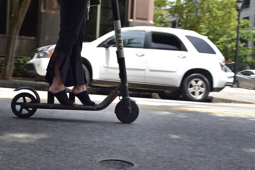 (AP Photo/Amanda Morris). In this May 28, 2019, photo, a woman rides an electronic scooter in downtown Raleigh, N.C. As electric scooters have rolled into more than 100 cities worldwide, many of the people riding them have ended up in the emergency roo...