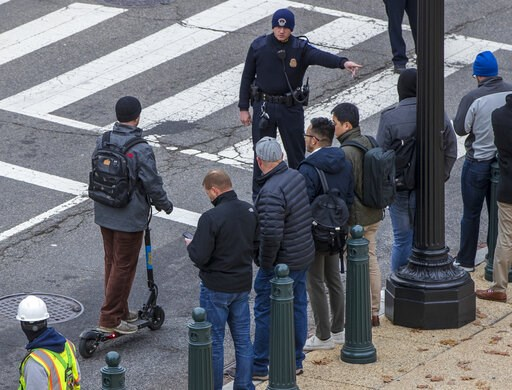 (AP Photo/J. Scott Applewhite). In this Dec. 5, 2018, photo, a police officer directs a rider on a Skip brand electric scooter to move off the street on Capitol Hill in Washington. As electric scooters have rolled into more than 100 cities worldwide, m...