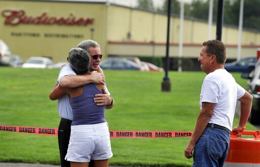 (AP Photo/Jessica Hill, File). FILE - In this Aug. 4, 2010, file photo, employees and friends gather outside of Hartford Distributors after a mass shooting by an employee in Manchester, Conn. The gunman called 911 as police closed in and told the opera...
