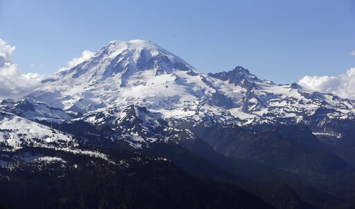 (AP Photo/Elaine Thompson, File). FILE - In this file photo taken June 19, 2013, Mount Rainier is seen from a helicopter flying south of the mountain and west of Yakima, Wash. A helicopter rescued four climbers from near the summit of Mount Rainier Thu...