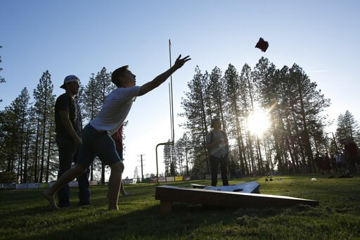 (AP Photo/Rich Pedroncelli). Sean Newsom, second from left, tosses a bean bag as he plays cornhole at the Paradise High School in Paradise, Calif., Wednesday, June 5, 2019. After the Camp Fire destroyed his family home in Paradise and his parents reloc...