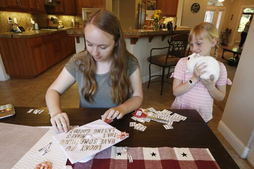 (AP Photo/Rich Pedroncelli). Emilee Taylor a senior at Paradise High School, decorates her graduation cap as her younger sister Baylee, 10, with her pet rabbit, Sebby, watches, at their home in Chico, Calif., Wednesday, June 5, 2019. After the Camp Fir...