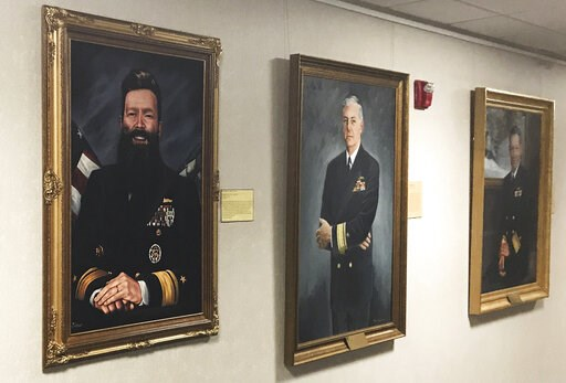 (Rear Adm. Jeffrey Harley/U.S. Naval War College via AP). This May 2019 photo provided by U.S. Naval War College president Rear Adm. Jeffrey Harley, shows his official artist's portrait, left, displayed in a gallery in Conolly Hall on the school's camp...