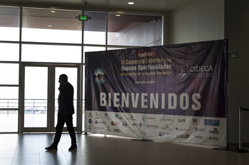 "(AP Photo/Hans-Maximo Musielik). A business man talks on the phone next to the welcome sign of the ""New Opportunities for Foreign Trade"" Symposium at the Rosarito Convention Center near Tijuana, Mexico, Friday, June 7, 2019. Companies have been rushing..."