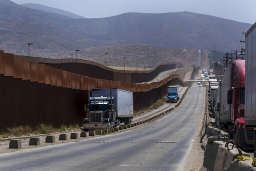 (AP Photo/Hans-Maximo Musielik). Trucks pass along a border wall as they get into position to cross into the United States at the border in Tijuana, Mexico, Friday, June 7, 2019. Companies have been rushing to ship as many goods as possible out of Mexi...