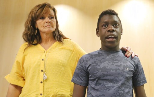 (AP Photo/Rick Bowmer). Jerri Hrubes stands next to her son DJ during a news conference Friday, June 7, 2019, in Salt Lake City. Hrubes is calling for an independent investigation after she says a police officer pointed a gun at her 10-year-old son's h...