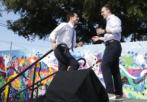 (AP Photo/Lynne Sladky, File). FILE - In this May 20, 2019, file photo, Democratic presidential candidate Pete Buttigieg, the mayor of South Bend, Ind., left, is introduced by his husband Chasten Glezman, right, during a fundraiser at the Wynwood Walls...