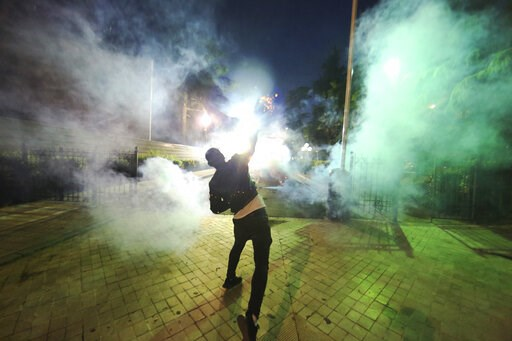 (AP Photo/Hektor Pustina). A demonstrator throws a flare toward Albanian police officers during an anti-government protest in Tirana, Albania, Saturday, June 8, 2019. Thousands of Albanian opposition supporters are gathering in an anti-government prote...