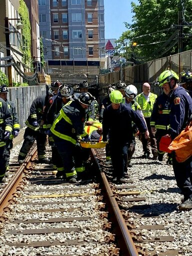 (Boston Fire Dept. via AP). This photo provided by the Boston Fire Department, Firefighters and EMT personnel carry an injured person after a train car derailed in Boston on Saturday, June 8, 2019.   Officials with the Massachusetts Bay Transportation ...
