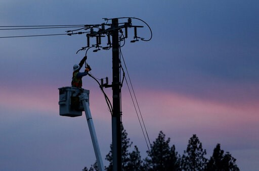 (AP Photo/Rich Pedroncelli, File). FILE - In this Nov. 26, 2018, file photo, a Pacific Gas & Electric lineman works to repair a power line in fire-ravaged Paradise, Calif.  Pacific Gas & Electric said it will shut off power Saturday, June 8, to...