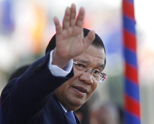 (AP Photo/Heng Sinith, File). FILE - In this Nov. 21, 2018, file photo, Cambodia's Prime Minister Hun Sen waves as he watches boat races during the water festival in Phnom Penh, Cambodia. The bitter decadeslong rivalry between Hun Sen, Cambodia's stron...