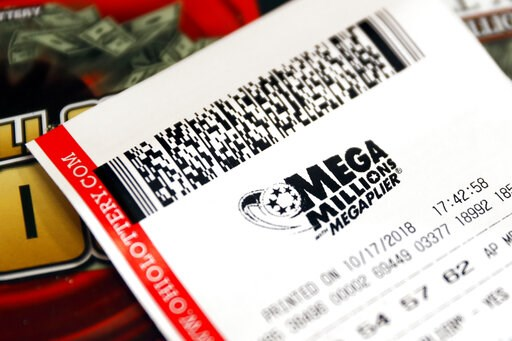 (AP Photo/John Minchillo, File). FILE - In this Oct. 17, 2018, file photo a Mega Millions lottery ticket rests on the shop counter at the Street Corner Market in Cincinnati. A lottery ticket worth $530 million in the Mega Millions draw was sold at a li...