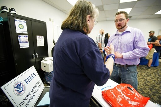 (AP Photo/Nati Harnik). In this April 25, 2019 photo, Lincoln veteran Scott Smith, right, talks to FEMA representative Kristina Pooler about available FEMA jobs, at a job fair in Lincoln, Neb. With federal disaster recovery staffers scrambling to meet ...